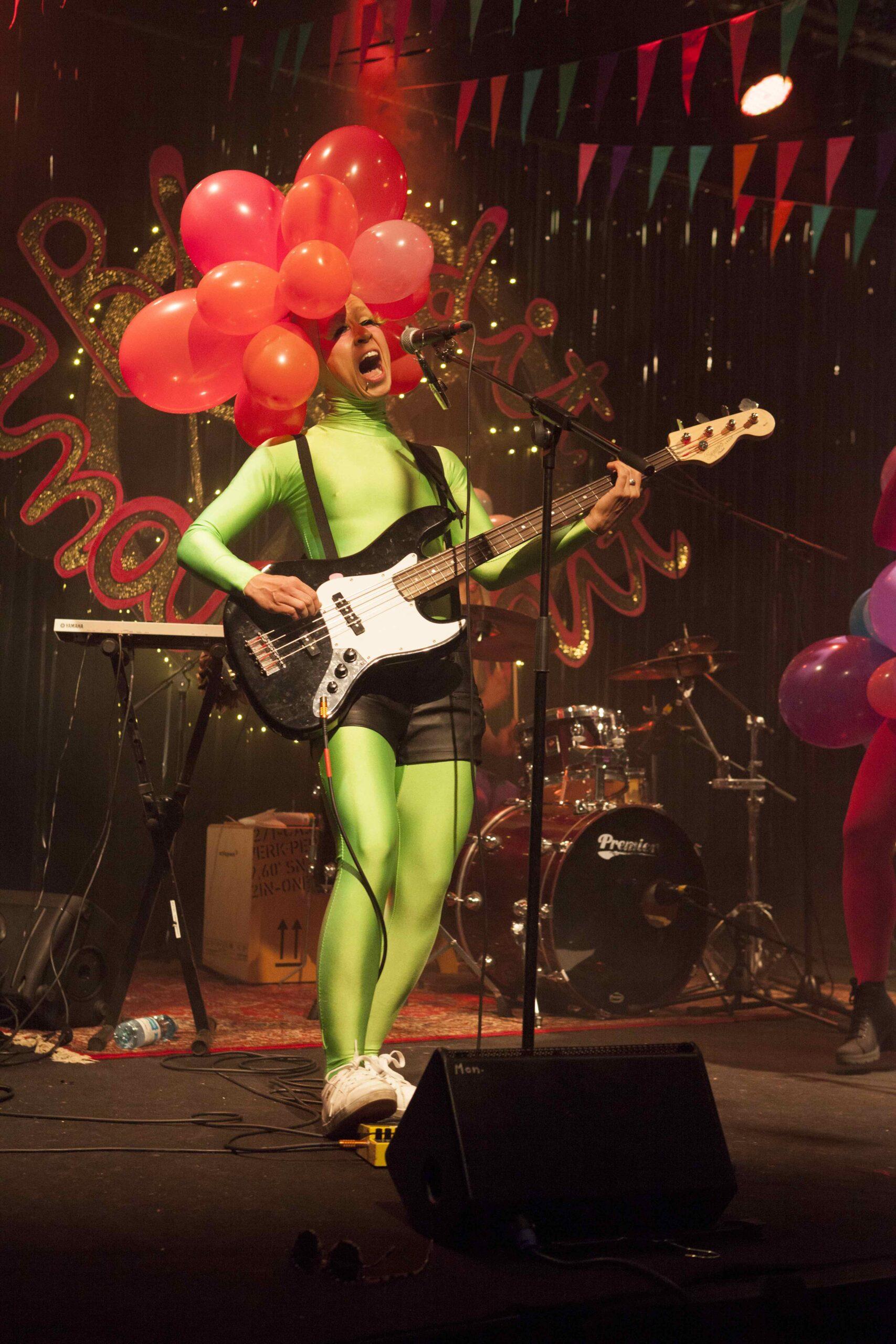 """Blondit amazoonit laulavat: """"Meitä tuijotetaan kaduilla, kun näytetään niin hyviltä."""" Ilmapalloihin ja spandexiin verhoutunut basisti-kitaristi Paula täyttää sanoituksen lupauksen Kapsäkin lavalla."""