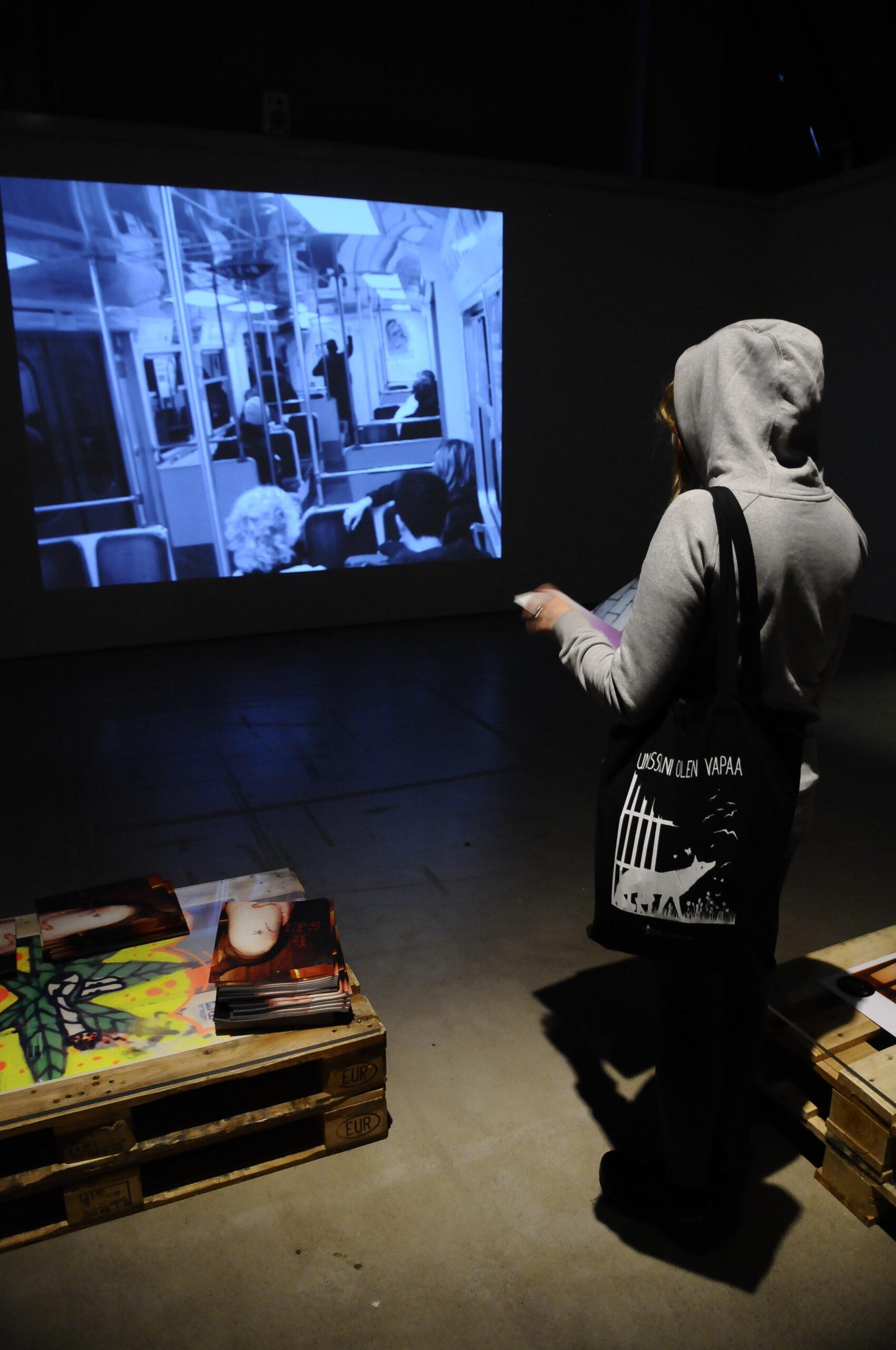 Katutaiteilija Nora Helsinki tutustui Graffiti-näyttelyn avajaisissa NUGin Territorial Pissing -videoon.