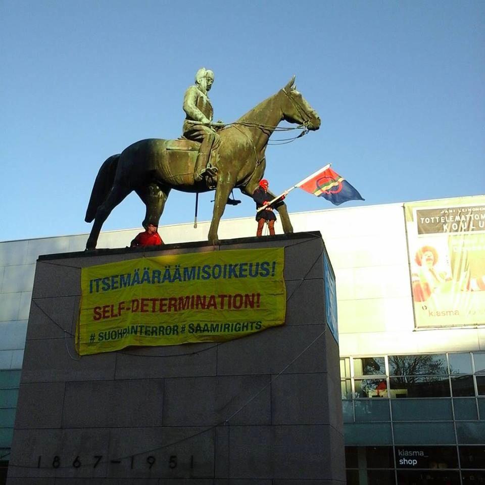 Suohpanterrorin Kiasmassa järjestetyn näyttelyn avajaisten yhteydessä ryhmän jäsen kiipesi Marskin patsaalle osoittamaan mieltään. KUVA: Suohpanterror