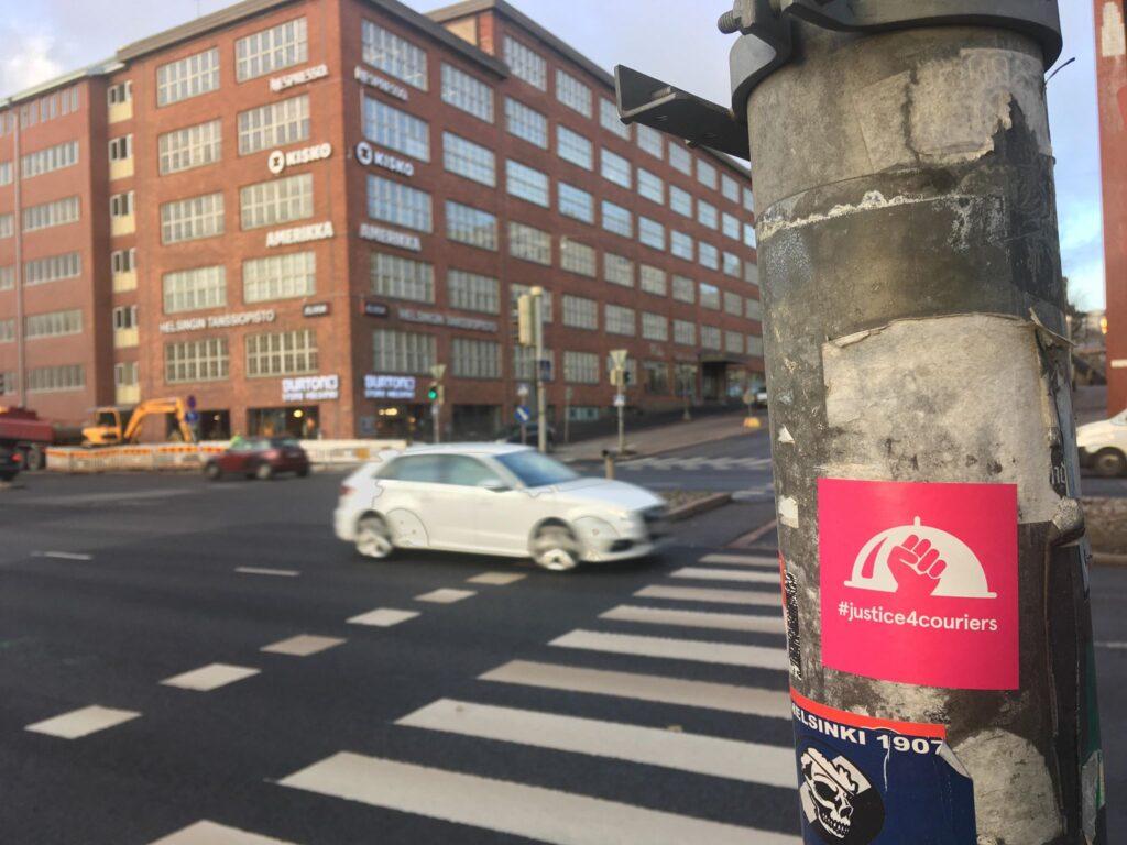 #justice4couriers-tarroja näkyy monissa liikennevalotolpissa ainakin Helsingissä. Useimmiten tarrat esiintyvät juurikin paikoissa, joissa polkupyöräilijät ylittävät autoteitä – ja odottavat vuoroaan valoissa.