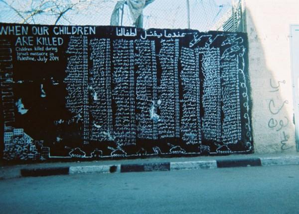 """""""Me muistamme heidät kunnes kuolemme itse."""" (Ghassan, 14) Seinämaalaukseen on kirjoitettu Gazassa kesällä 2014 surmattujen lasten nimiä."""