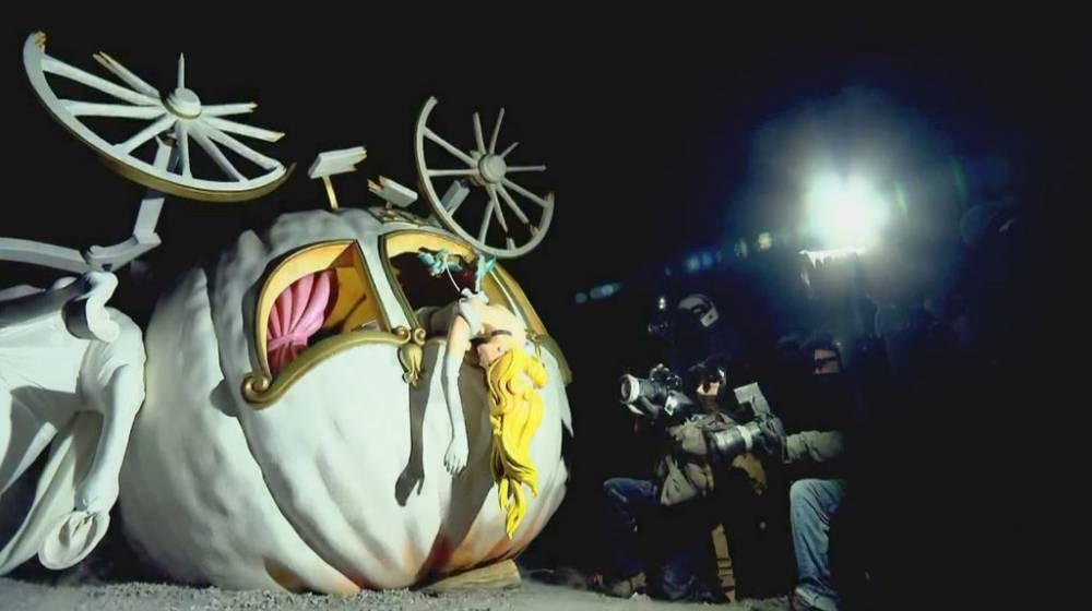 Kolarissa kuollut Tuhkimo. Sotakuvaava-paparazzien salamavalot valaisevat Tuhkimon kellistyneet vaunut. Ensijärkytyksen jälkeen katsoja voi pohtia Banksyn teoksen äärellä satujen ja nykyisten kuningashuoneiden elämän välistä jännitettä.