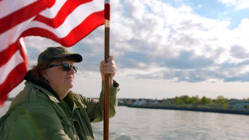 Michael Moore heiluttaa tähtilippua liberaalin USA:n puolesta