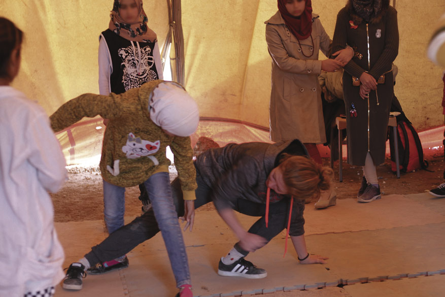 Tyttöjen capoeira-tunti hiekkaa pöllyävässä teltassa.