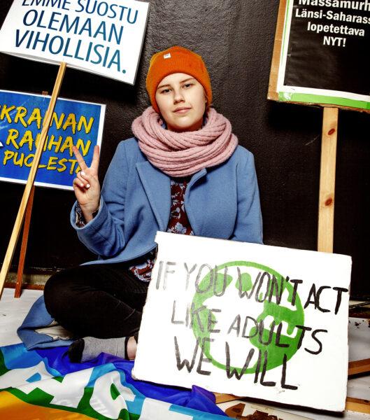 Falenius istuu maassa mielenosoituskylttien ympärillä, katsoo hymyillen kameraan. Tekee sormillaan peace-merkin.