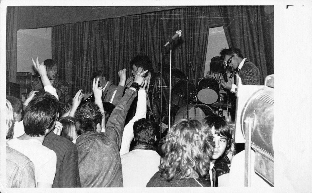 Mustavalkokuva jossa Vennaskond yhtye soittaa pienellä lavalla. Yleisöllä kädet ilmassa.