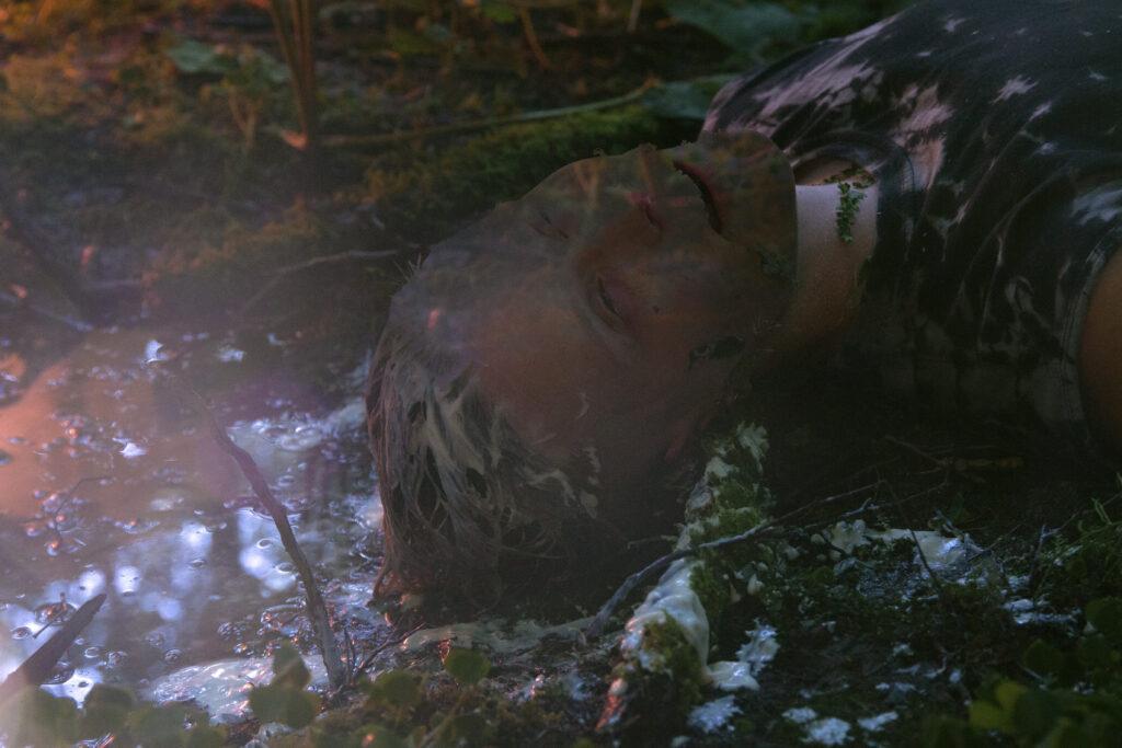 Taidekuva jossa henkilö makaa metsässä. Kasvojen läpi heijastuu metsän tekstuuria.