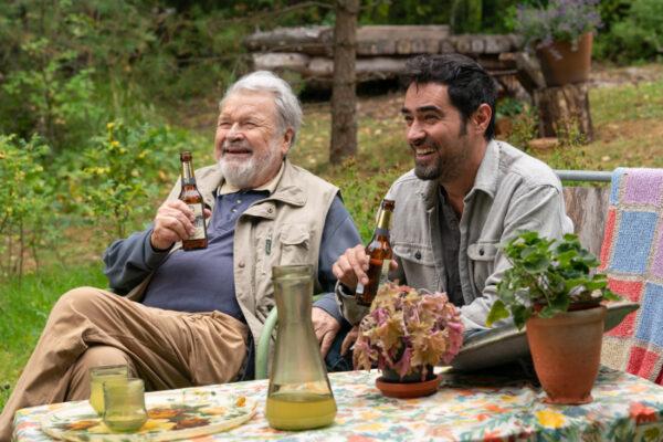 Kaksi nauravaa, olutta juovaa henkilöä istuu puutarhassa pöydän ääressä.