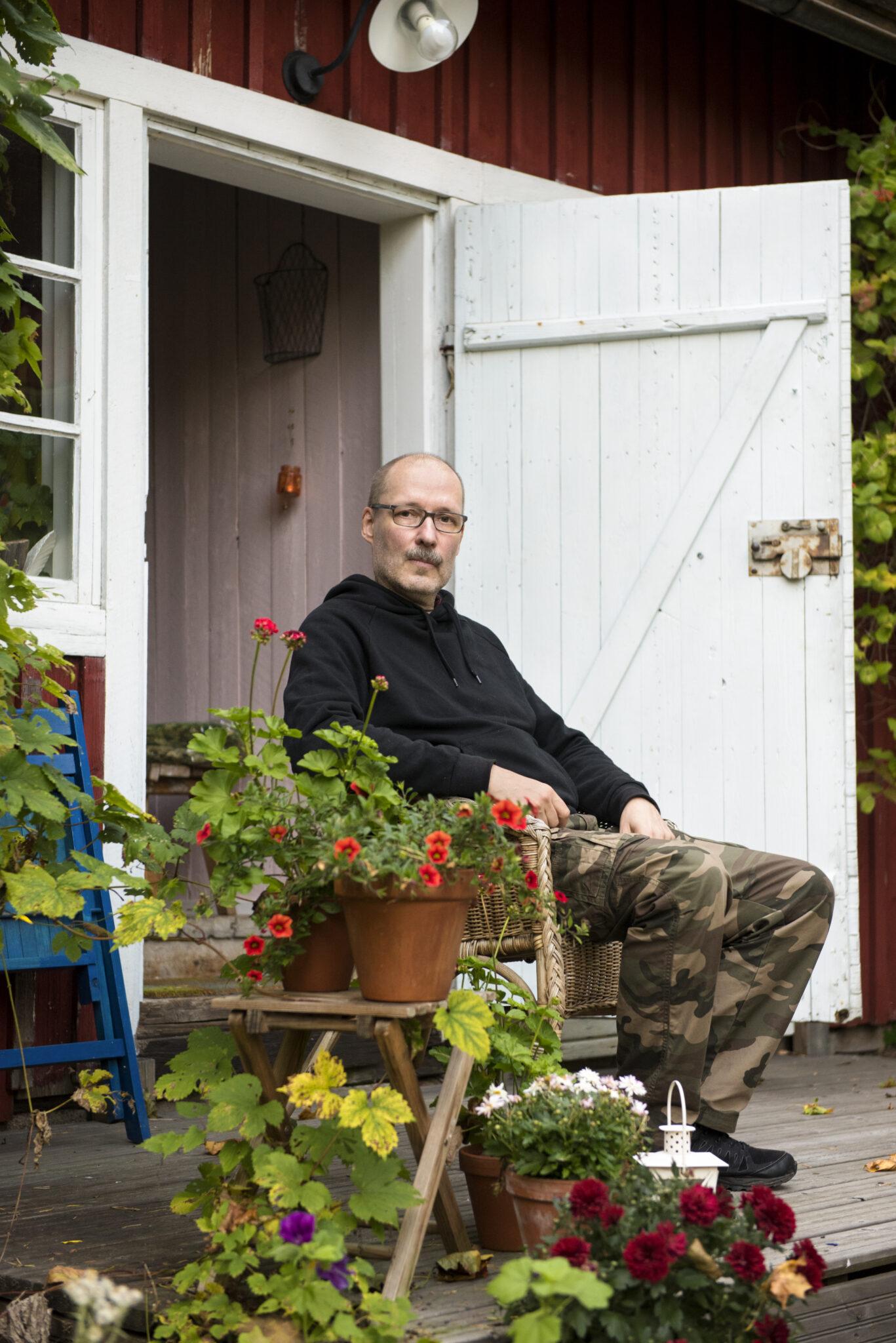 Kärkkäinen istumassa kuistilla maastohousut jalassa päällä huppari. Etualalla kukkia.