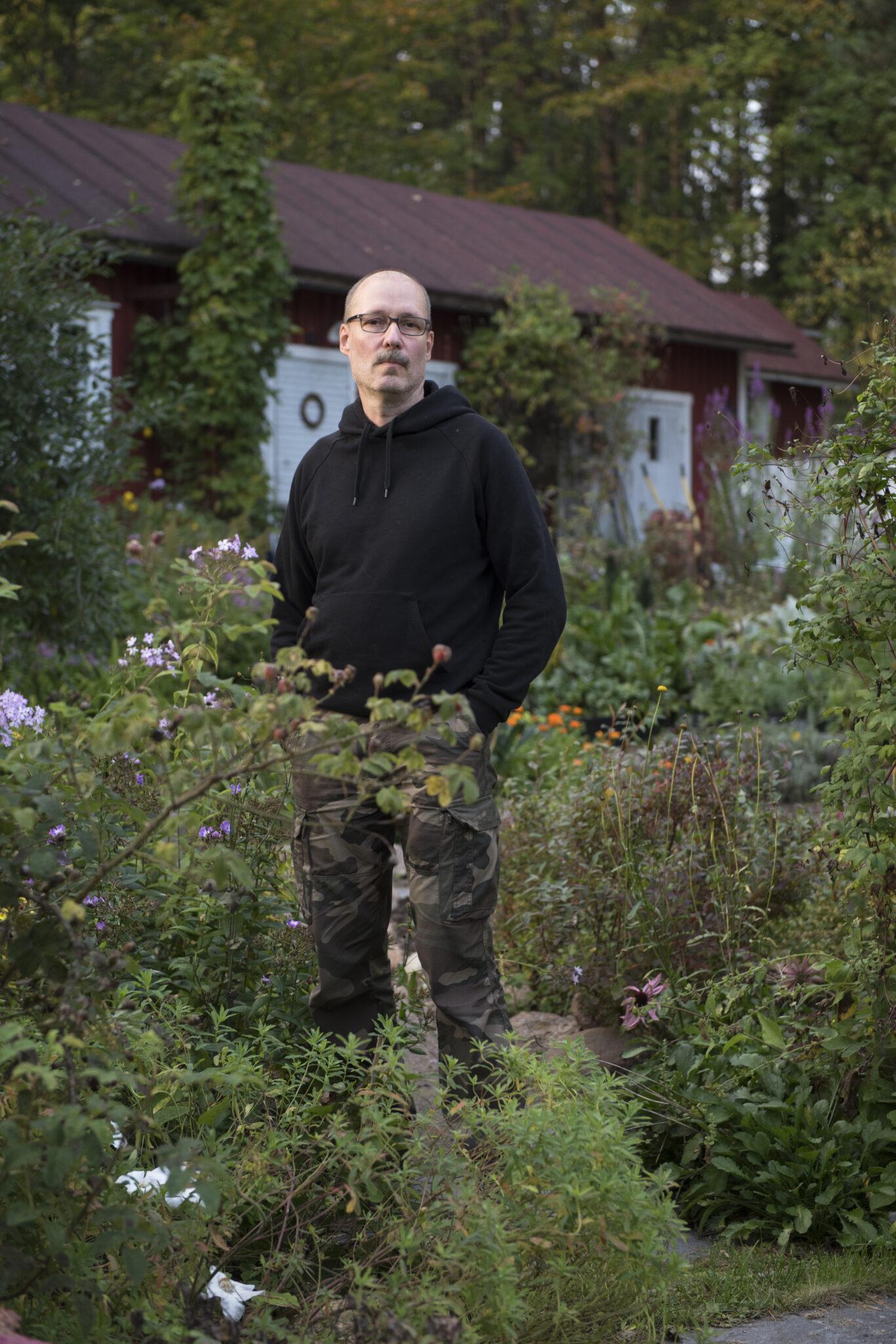 Kärkkäinen seisomassa puutarhassa kädet maastohousujen taskuissa. Musta huppari päällä. Taustalla punainen ulkorakennuksen seinä.