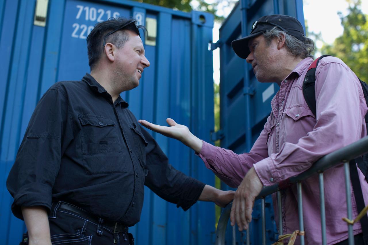 Mustaan kauluspaitaan pukeutunut Tonu Trubetsky keskustelemassa. Takana sininen laivakontti.