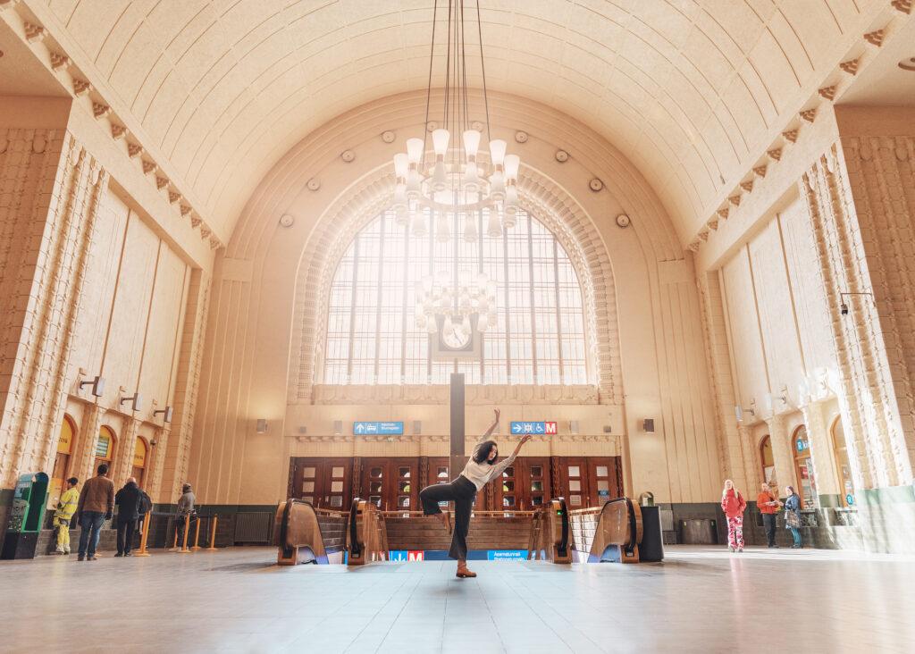 Aldebs tanssii Helsingin päärautatieaseman aulassa. Halliin paistaa aurinko.