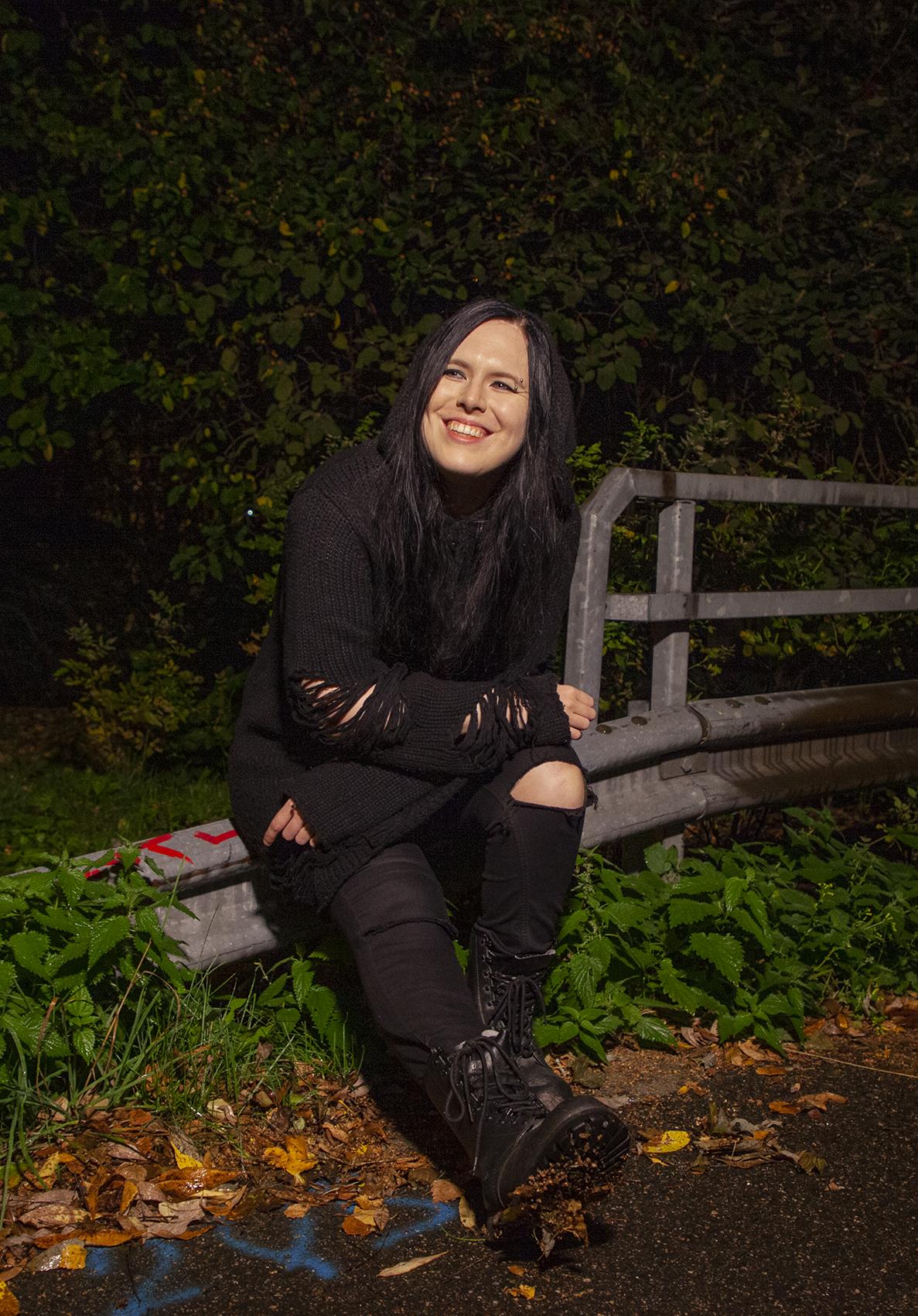 Söderholm istuu metallikaiteella pimeällä. Päällä musta revitty neule ja polvesta rikkinäiset tummat. farkut.