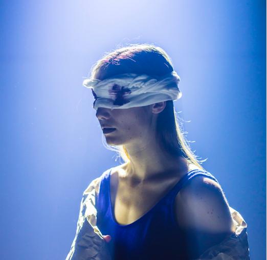 Naisoletettu näyttelijä side silmillä sinistä taustaa vasten. Silmien kohdalla verta.