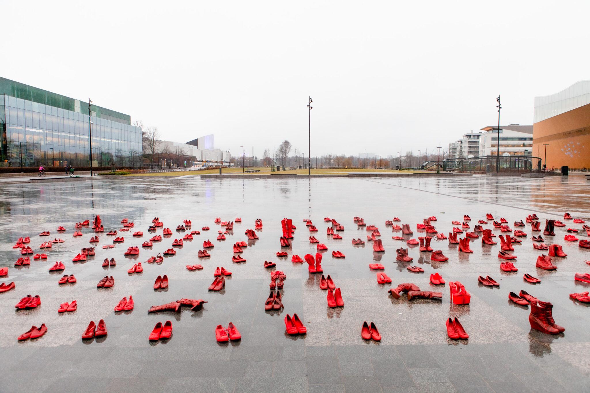 Monia punaiseksi maalattuja kenkiä aseteltuna sateen kastelemalle asfaltille. Taustalla Musiikkitalo ja Oodi.