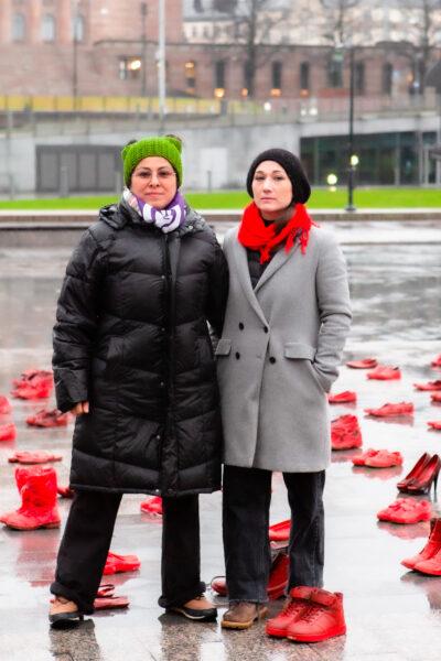 Monia punaiseksi maalattuja kenkiä aseteltuna sateen kastelemalle asfaltille. Kaksi henkilöä seisoo kenkien keskellä.