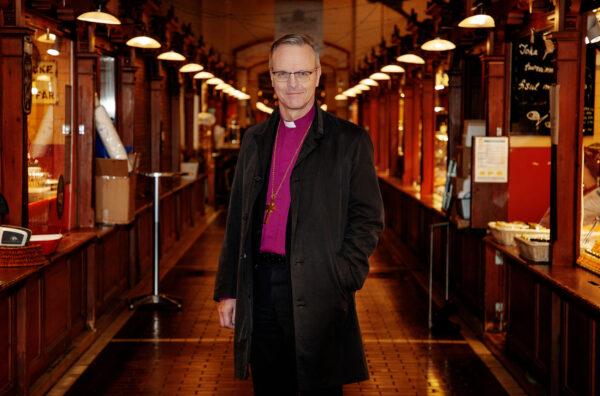 Arkkipiispa seisoo kauppahallin käytävällä.