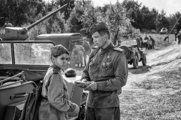 Mustavalkoinen kuva, nuori poika seisoo sotilaan vieressä. Taustalla panssarivaunu, autoja.
