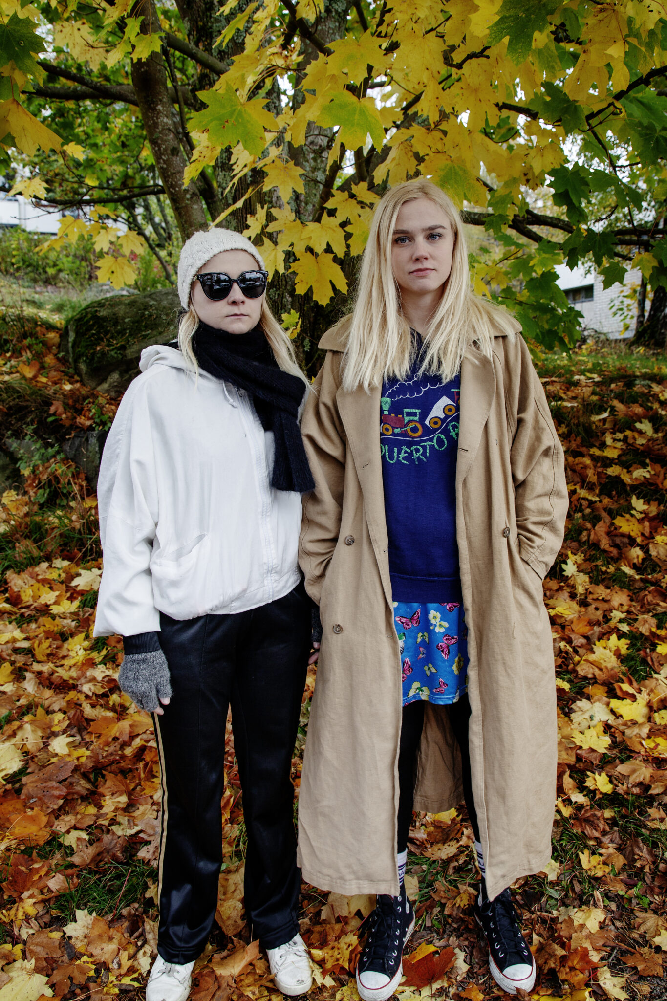 Anna ja Kaisa seisovat vierekkäin. Maassa pudonneita lehtiä.