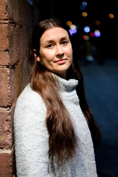 Tiina Elovaara katsoo kameraan hymyillen, Helsingin rautatieaseman laiturialueella valon alla. Taustalla pimeää.