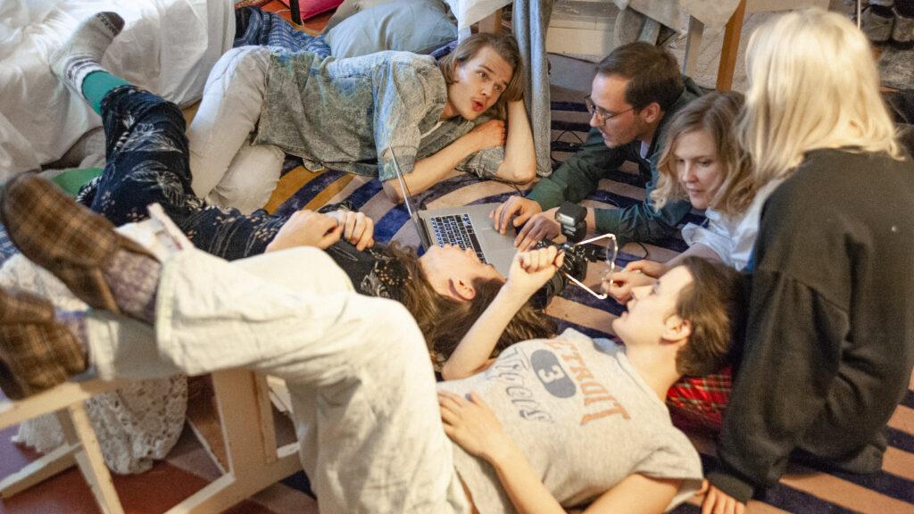 Joukko makaa lattialla, keskellä läppäri ja kamera.
