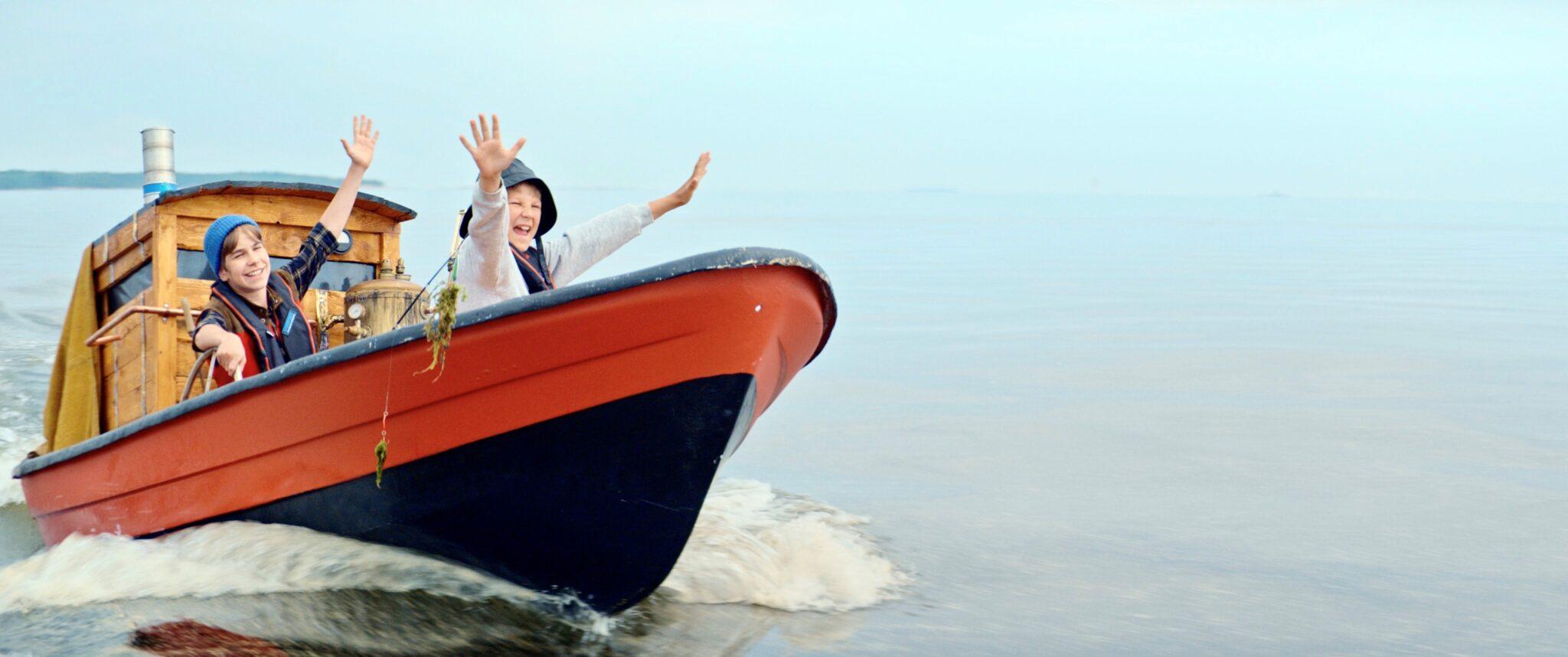 Kaksi iloista lasta veneessä, heiluttavat käsiä.