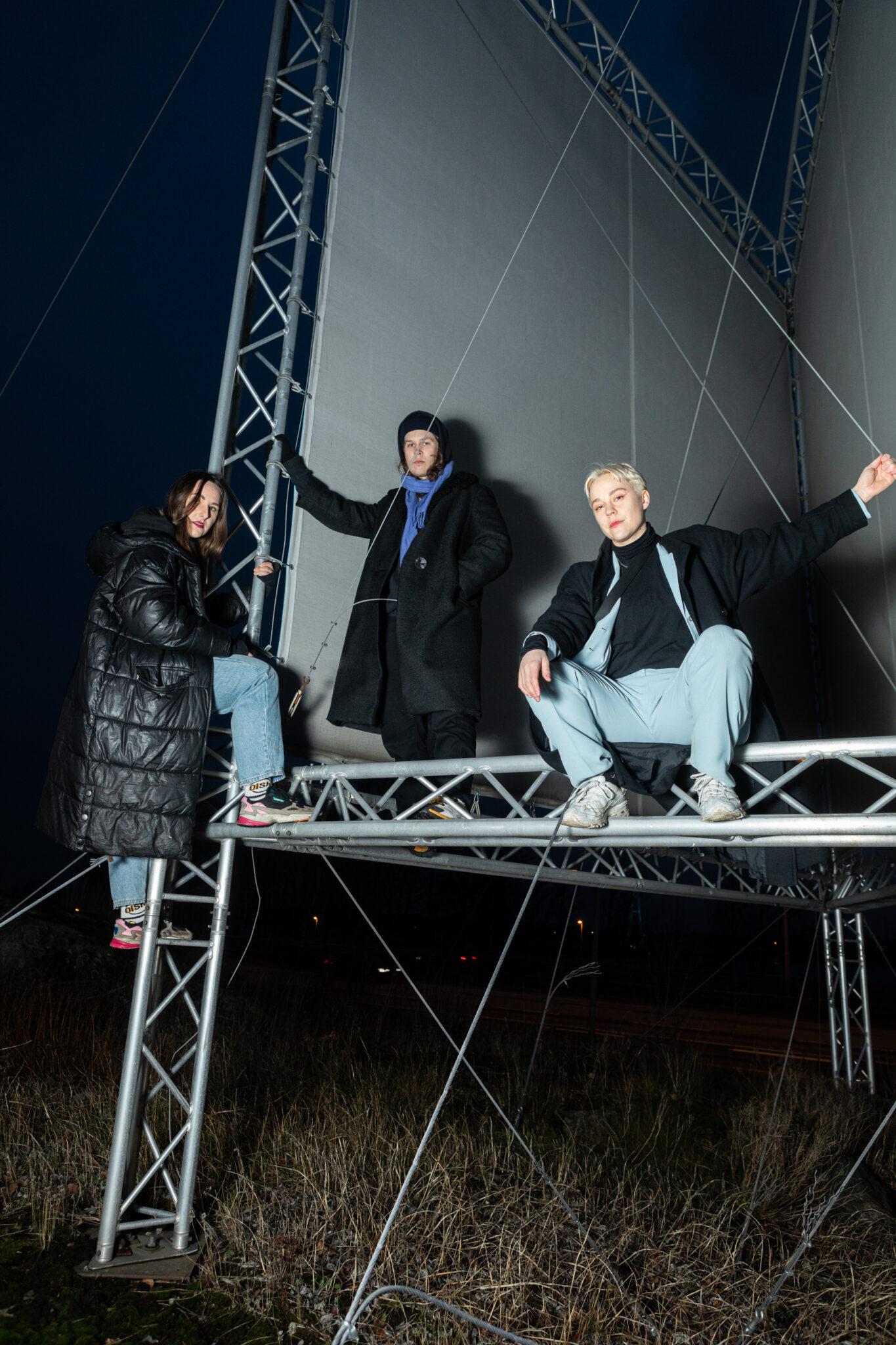 Yhtyeen jäsenet ovat kiivenneet isoon tienvarsimainokseen jossa poseeraavat kameralle. Taustalla öinen taivas.