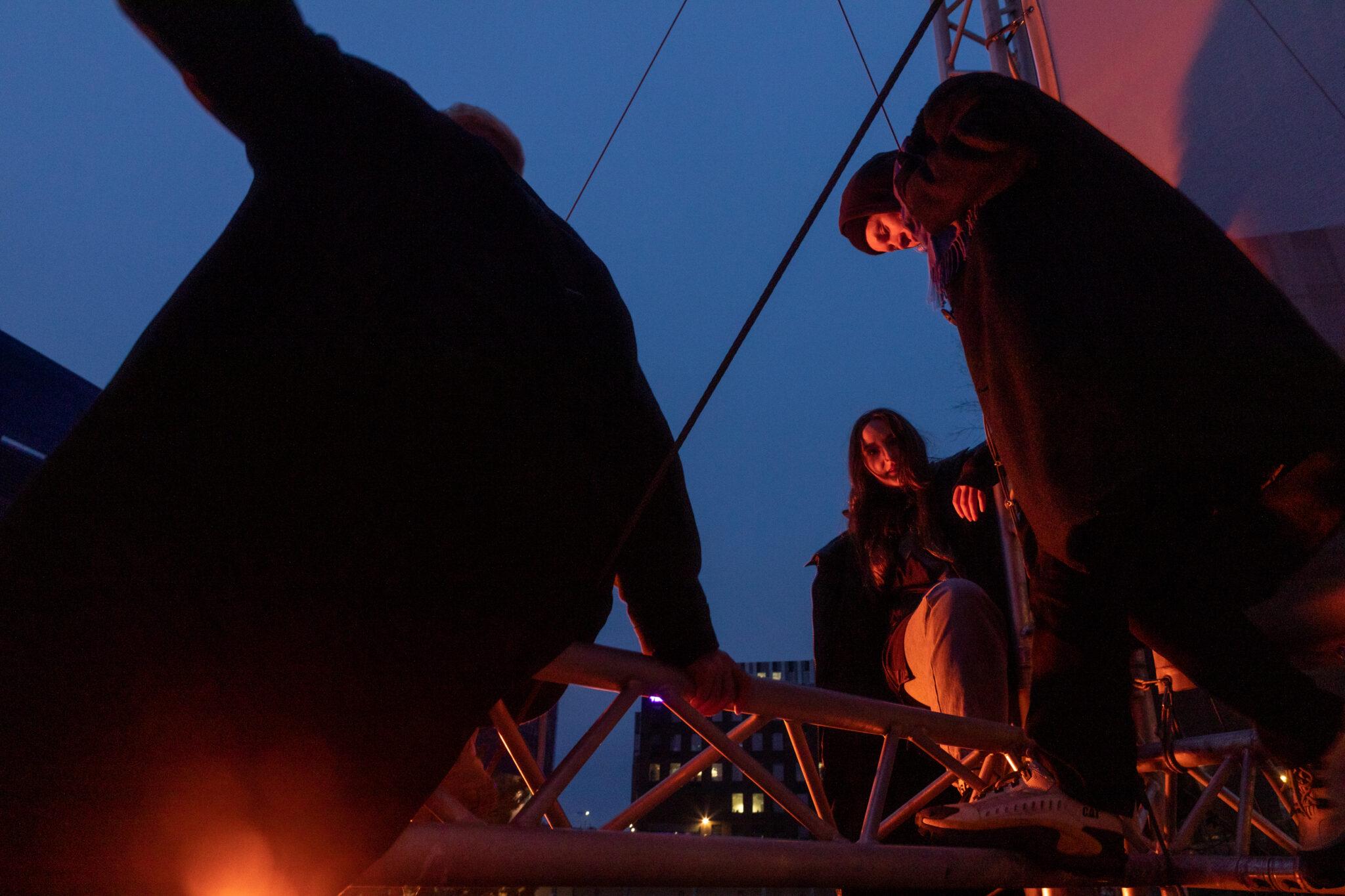 Yhtyeen jäsenet kuvattuna pimeää taivasta vasten. Taustalla kaupungin valoja.