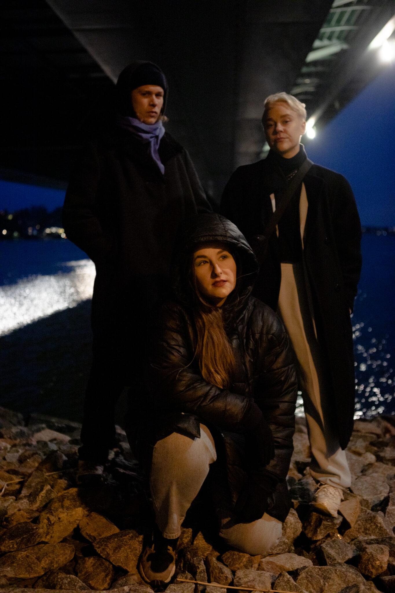 Yhtyeen jäsenet sillan alla, taustalla meri. Etualalla Vane Vane kyykistyneenä. Liki ja Kaisa Cleva seisovat vierekkäin taustalla.