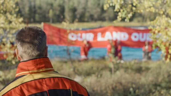 """Saamenpukuisen henkilön niska kuvan etualalla, taustalla luontoa ja mielenosoittajia ja kyltti """"our land our-""""."""