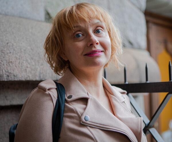 Maria Säkö katsoo kameraan. Päällään vaalea takki, takana kiviseinä.