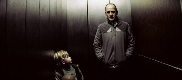 Lapsi katsoo aikuista hämärässä hississä.