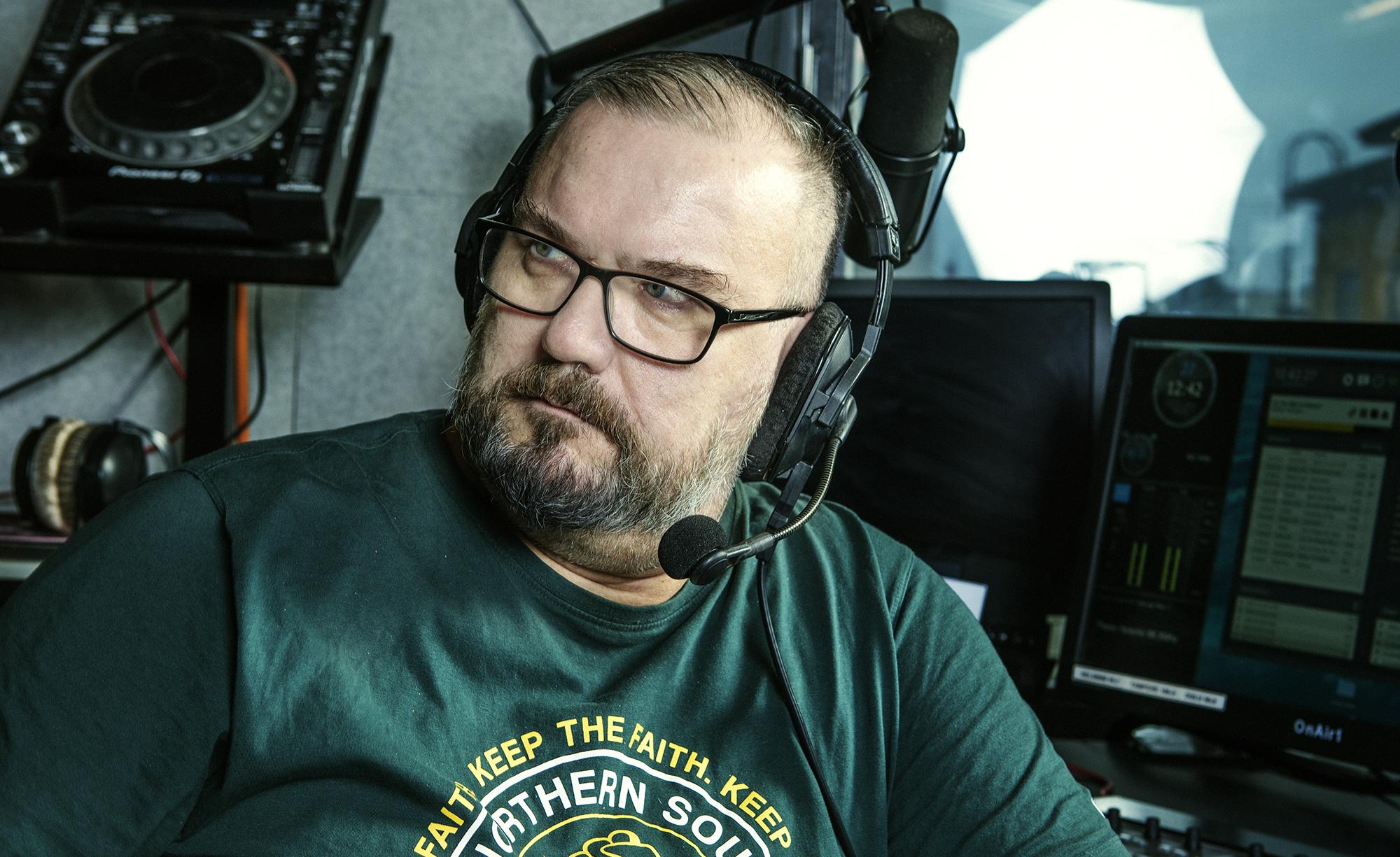 Njassa mikrofonilliset kuulokkeet päässä. Yllään vihreä t-paita.