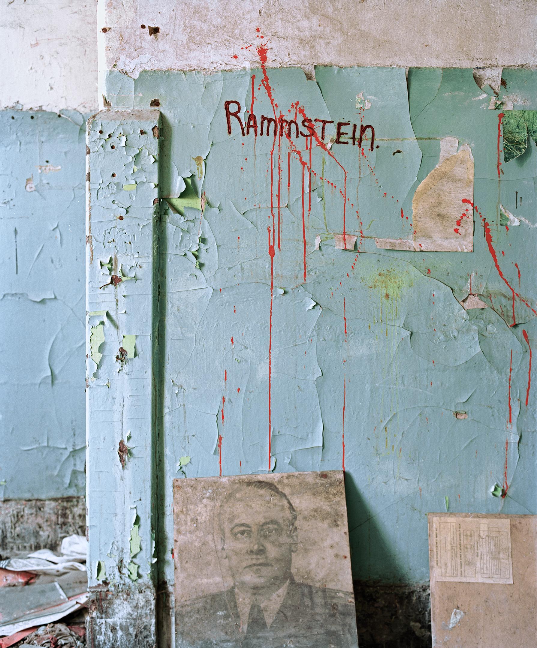 """Maali on rapissut turkoosista seinästä johon roiskunut punaista maalia ja kirjoitettu """"Rammstein"""""""