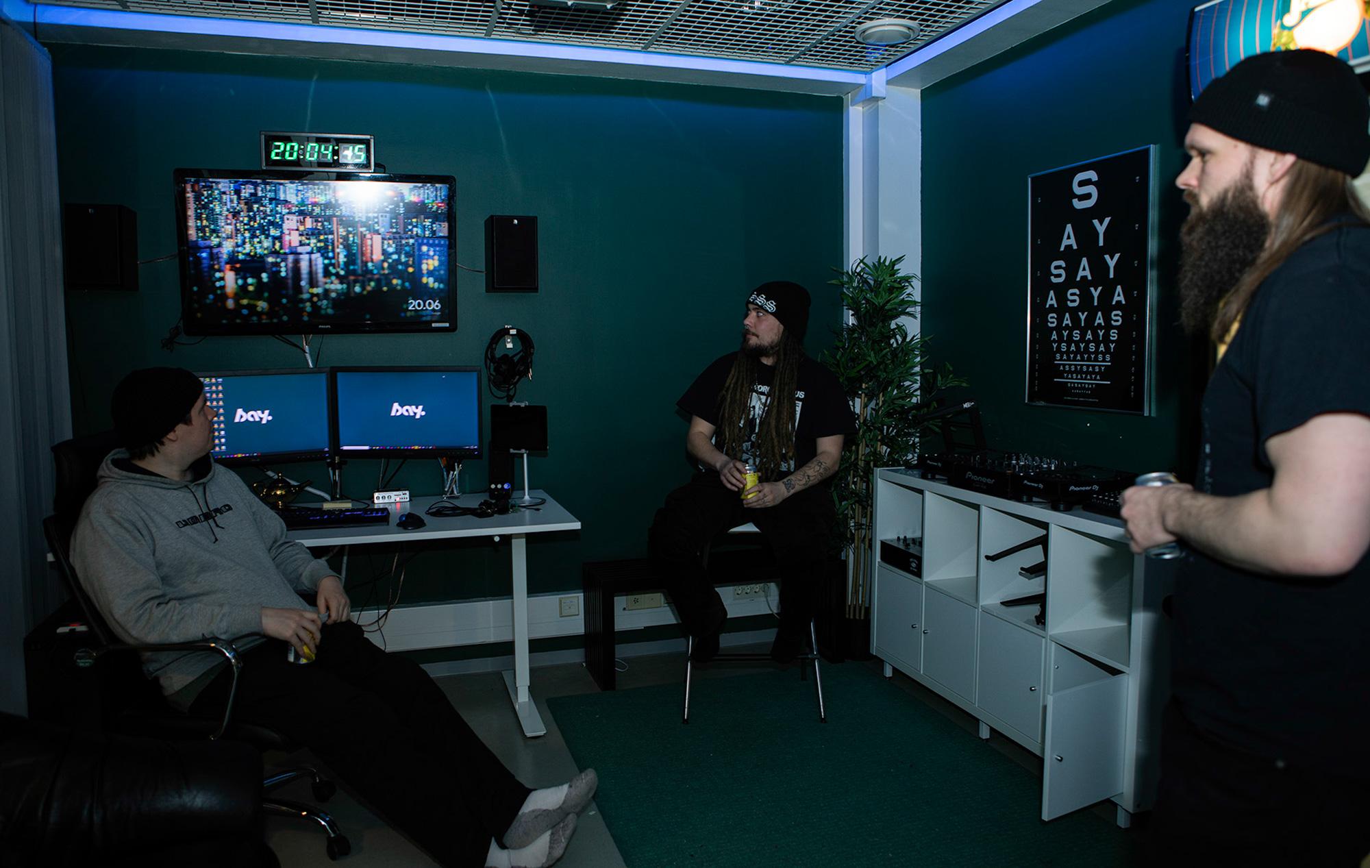 Kolme miestä hengailee sinisesti valaistulla studiolla näyttöruutujen ääressä oluttölkit kädessä.