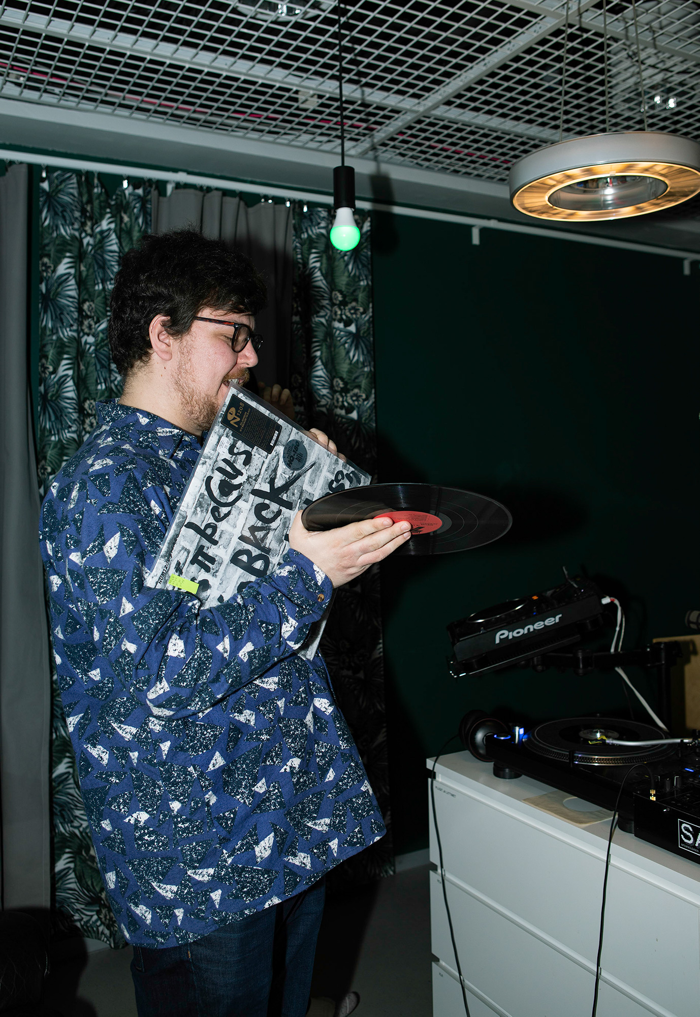 DJ pitelemässä vinyylilevyä kädessään ja kantta hampaissaan. Päällä sininen kauluspaita.