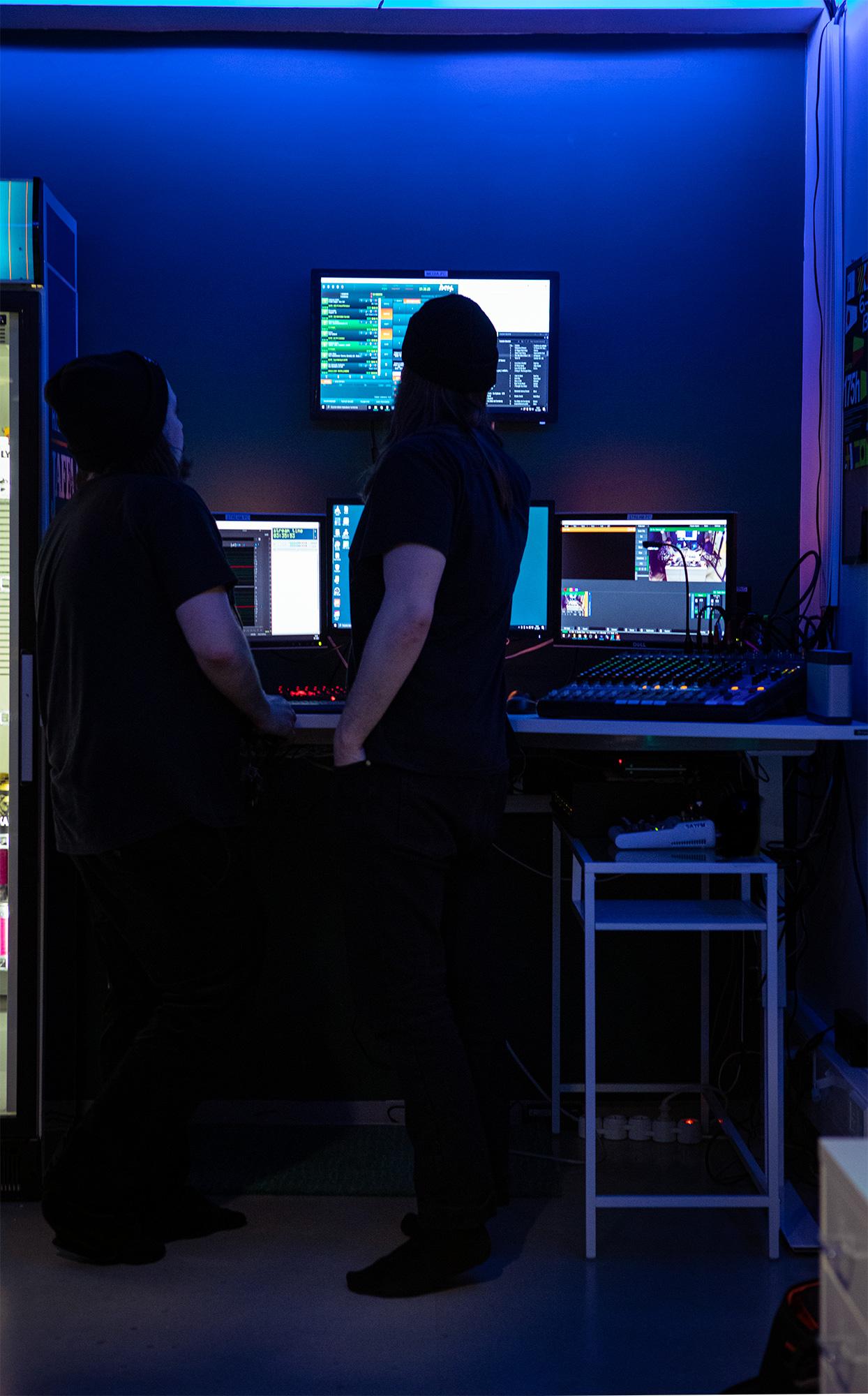 Kaksi mustiin pukeutunutta pipopäistä miestä tutkimassa studion näyttöruutuja