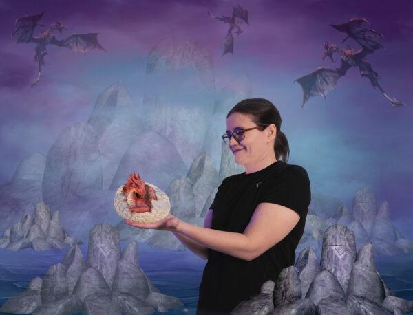 Stella Härkönen liitettynä pelimaailmaa. Taivaalla lentelee lohikäärmeitä ja hän pitää itse munasta kuoriutunutta lohikäärmeen poikasta käsissään.