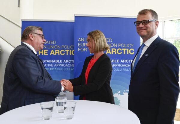 Timo Soini kättelemässä Federica Mogherinia. Juha Sipilä katsoo kohti kameraa ja hymyilee.