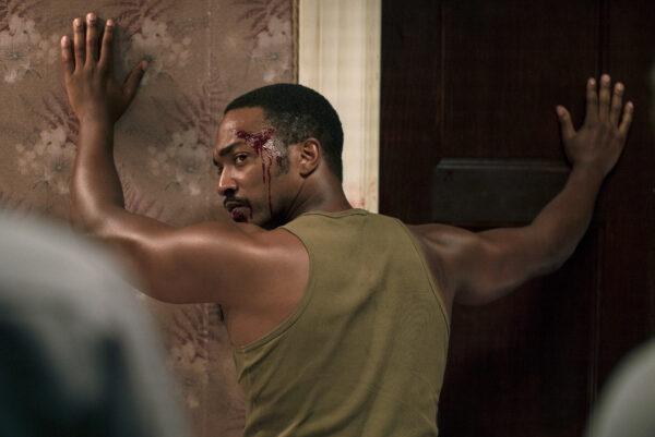 Musta henkilö pitelee käsiään seinää vasten. Katsoo olkansa yli. Päästä vuotaa verta.