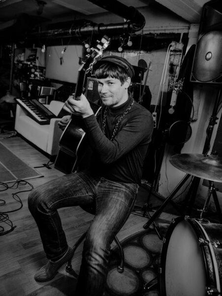Tanner studiolla, katsoo kameraan hymyillen ja pitelee kitaraa. Mustavalkoinen kuva.
