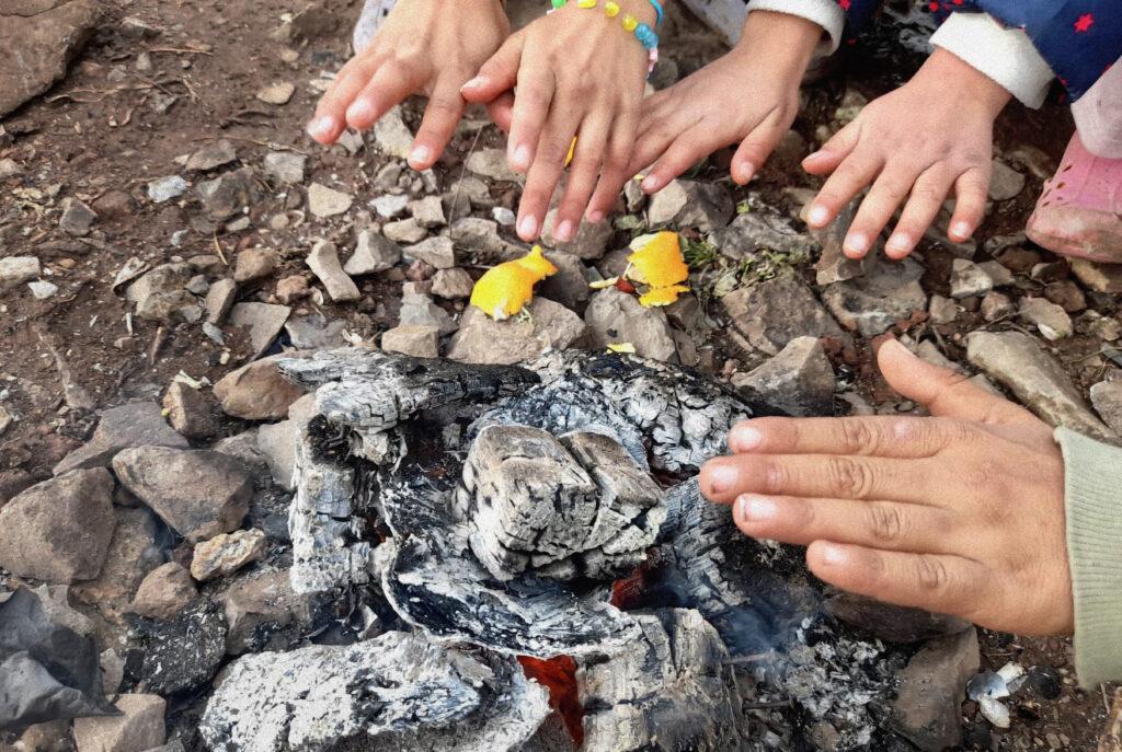 Lapset lämittelevät käsiään nuotiolla, lähikuva käsistä.