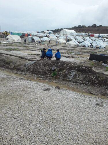 Kolme lasta, taustalla telttoja.