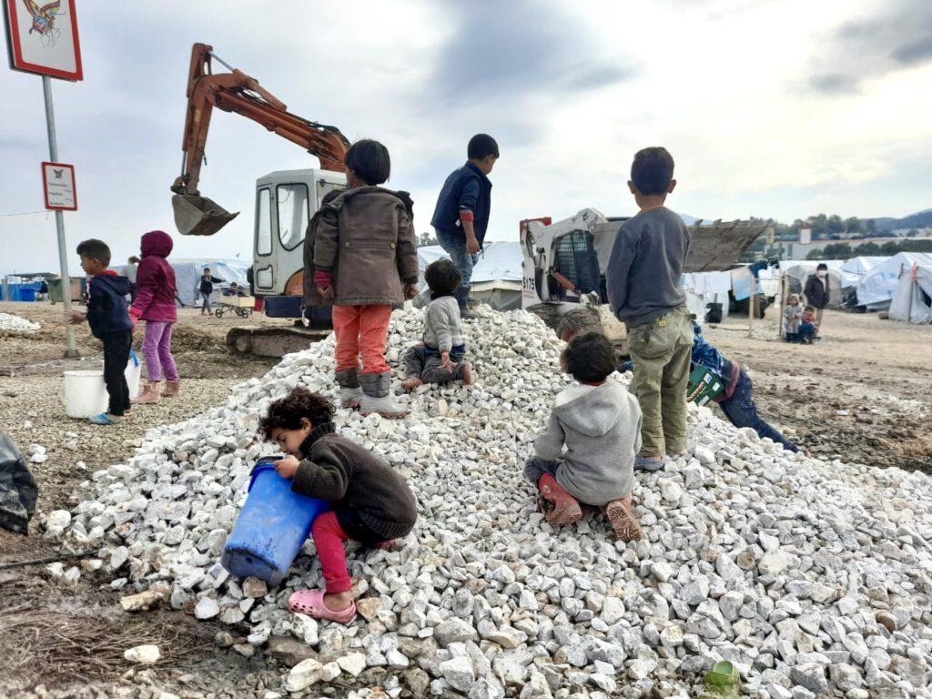 Lapset ovat kivikasan päällä, jotkut keräävät kiviä ämpäriin.