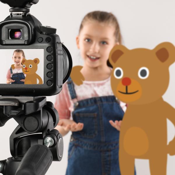 Lapsi puhuu studiossa kameralle, digitaalisesti tuotettu nalle vieressä.