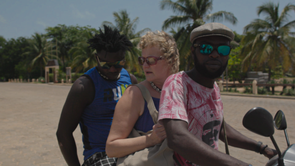 Valkoinen henkilö istuu kahden mustan henkilön välissä mopon kyydissä. Taustalla palmuja ja hiekkaa.
