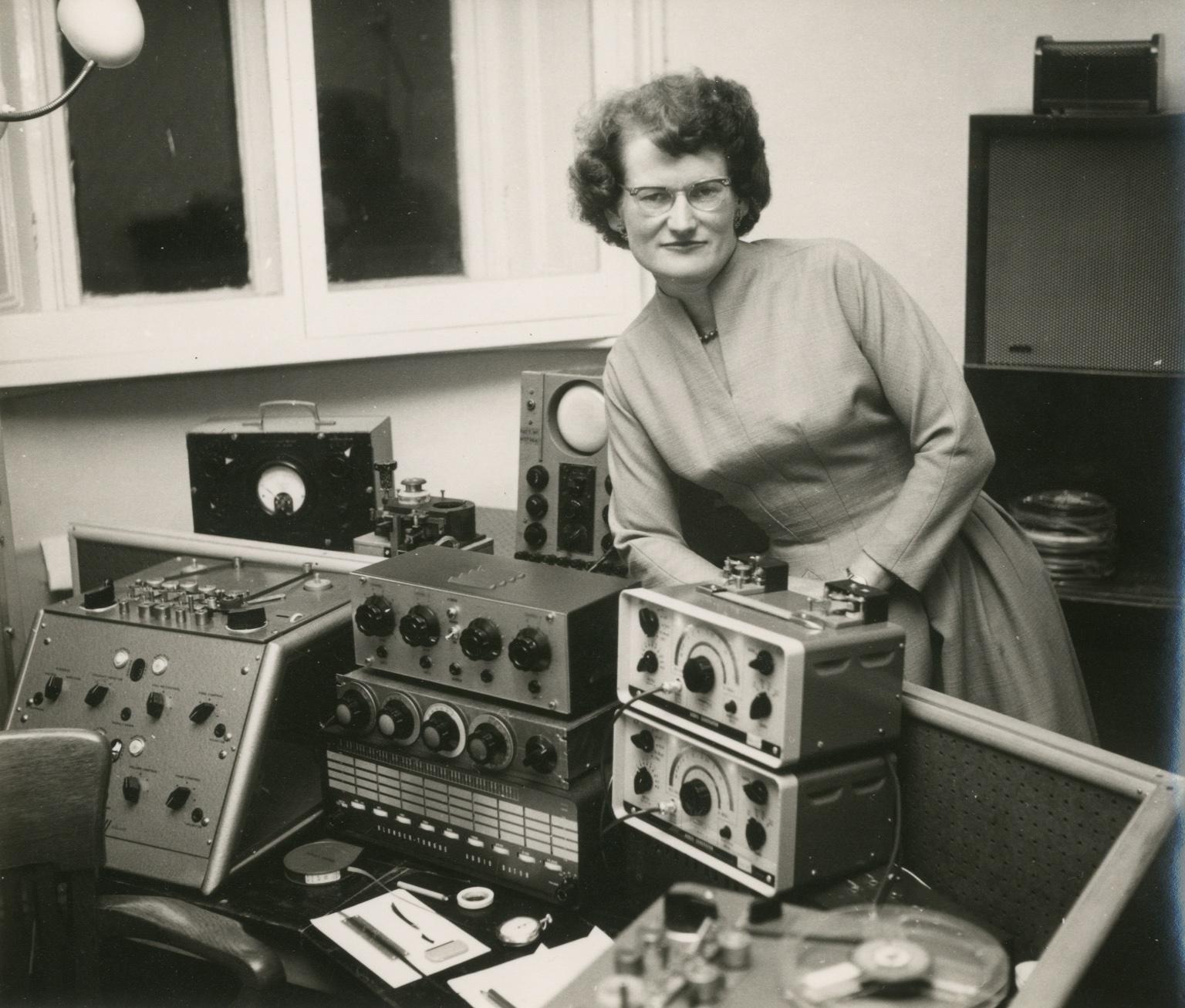 Mustavalkoinen kuva. Daphne Oram seisoo äänilaitteiden takana studiotiloissa.