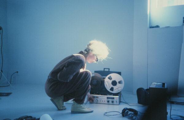 Sivusta kuvattu nainen polvistuneena lattialle äänilaitteen viereen.