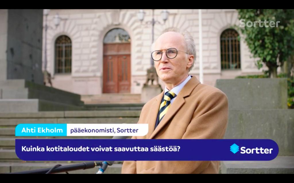 Ruskeaan villakangastakkiin pukeutunutta vanhempaa miestä haastatellaan Suomen pankin edessä