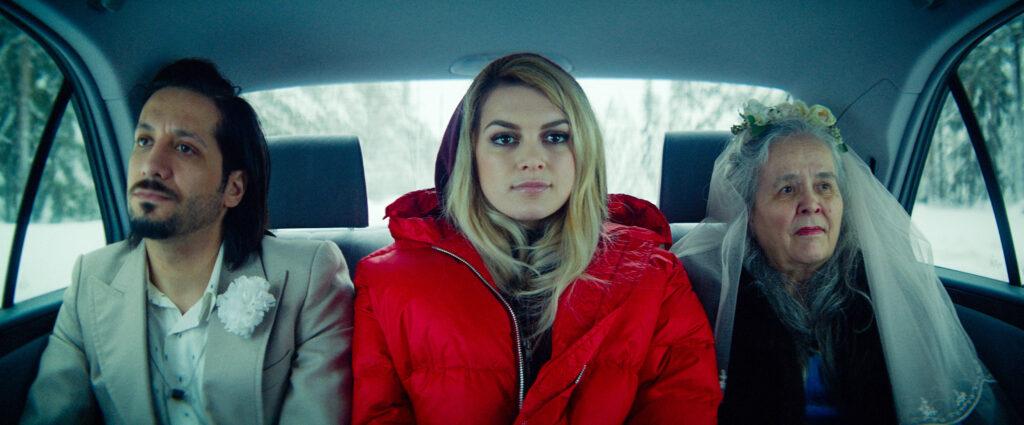 Kolme henkilöä istuu auton takapenkillä,